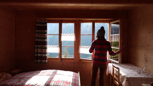 A woman taking a photo with her cellphone from the window of her chalet in the Swiss Alps.