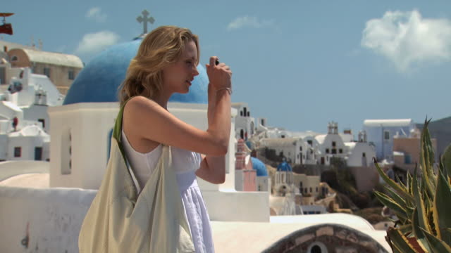 a woman taking a picture in santorini - see other clips from this shoot 1144 stock videos & royalty-free footage