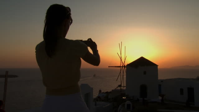 a woman taking a picture of a windmill in mykonos - see other clips from this shoot 1144 stock videos & royalty-free footage