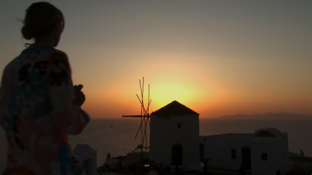 A woman taking a picture of a windmill in Mykonos