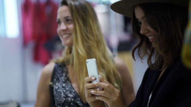 Frau, die ein Bild von ihrer Freundin, die Kleidung im Laden anprobieren