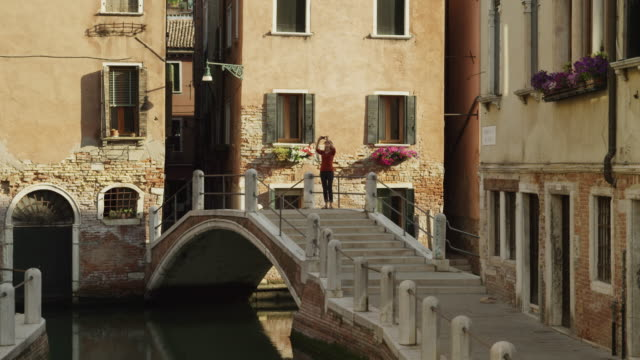 ws woman taking a picture on footbridge over canal,photographing / venice - venedig stock-videos und b-roll-filmmaterial
