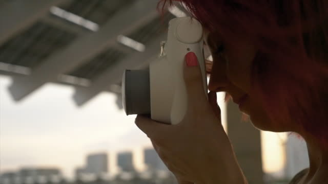 woman taking a picture with a instant camera - polaroid video stock e b–roll