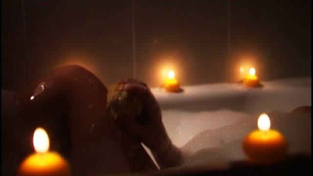 vidéos et rushes de woman taking a relaxing candle-lit bath - baignoire
