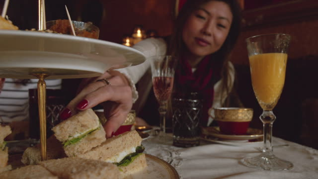 a woman taking a sandwich, while enjoying a high tea afternoon in melbourne - noelia ramon stock videos & royalty-free footage