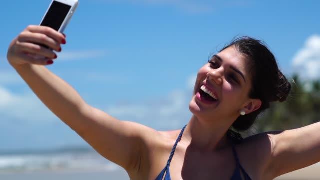 vídeos y material grabado en eventos de stock de mujer tomando un selfie en playa - américa del sur