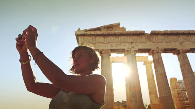 woman taking a selfie in front of parthenon - parthenon athens stock videos and b-roll footage