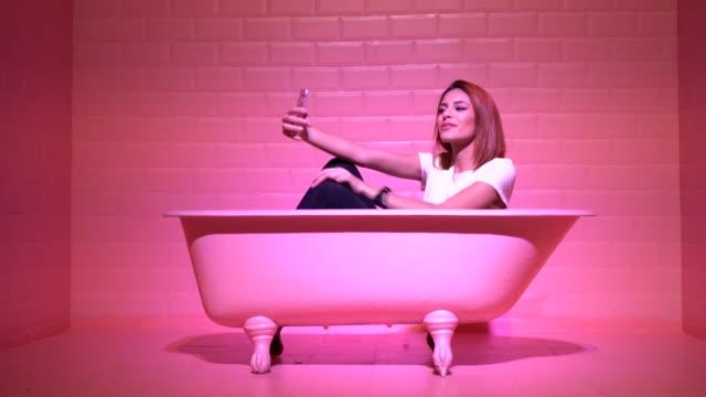 Woman Taking a Selfie in the pink bathtube