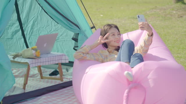 woman taking a selfie on an inflatable air bed in the han river park - inflatable stock videos & royalty-free footage
