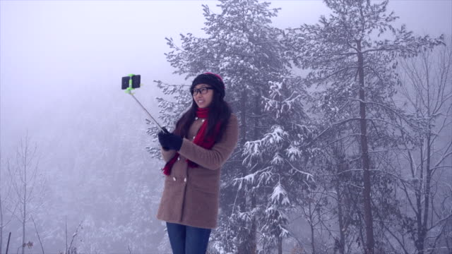 Woman taking a selfie stick in winter