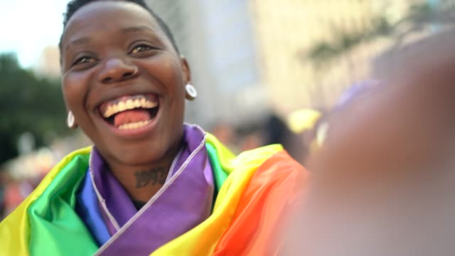woman taking a selfie using rainbow flag during lgbtqi parade - gay pride stock videos & royalty-free footage