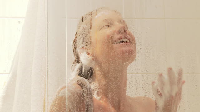 woman taking a shower - shampoo per capelli video stock e b–roll