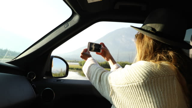 a woman taking a smartphone photo from a car pulled off to the side of the road. - sitta bildbanksvideor och videomaterial från bakom kulisserna