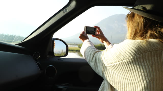 a woman taking a smartphone photo from a car pulled off to the side of the road. - activity stock videos and b-roll footage