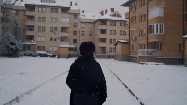 woman taking a walk while it's snowing - winter coat stock videos & royalty-free footage