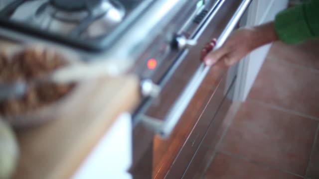 vídeos de stock e filmes b-roll de woman taking baked fruit dish out of oven - fazer doces