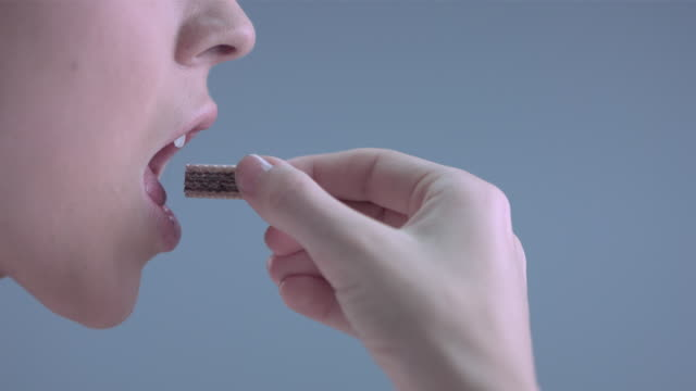 stockvideo's en b-roll-footage met cu slo mo woman taking bite from wafer - bijten