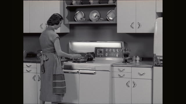 ms ts woman taking eggs from refrigerator then cracking eggs into frying pan / united states - bricco per il caffè video stock e b–roll