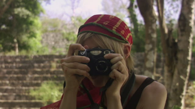 cu woman taking flash photograph toward camera near steps at mayan ruins / merida, mexico  - anno 2007 video stock e b–roll