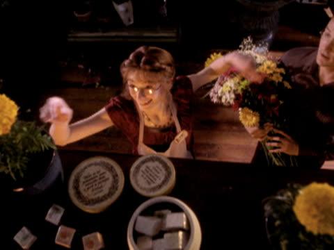 vidéos et rushes de ms ha woman taking flower off shelf and giving it to man, new zealand - fleuriste