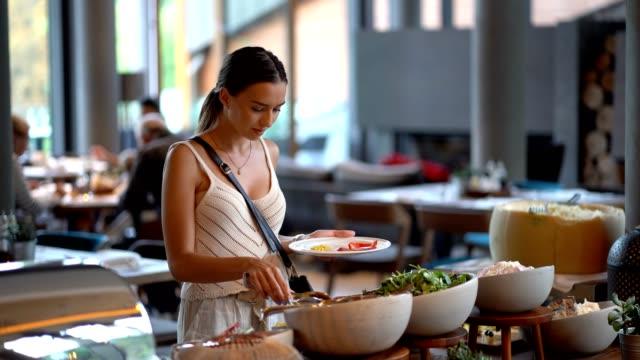 frau nimmt essen von einer buffetlinie - aussuchen stock-videos und b-roll-filmmaterial