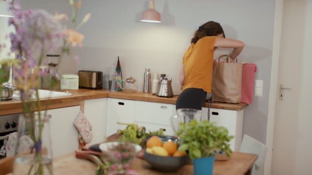 woman taking fruit out of paper shopping bag in kitchen - paper bag stock videos & royalty-free footage