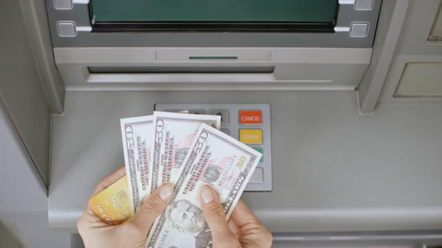 vídeos de stock, filmes e b-roll de ld mulher tomando seu dinheiro do dispensador de dinheiro no caixa eletrônico e deixando - nota de dólar americano