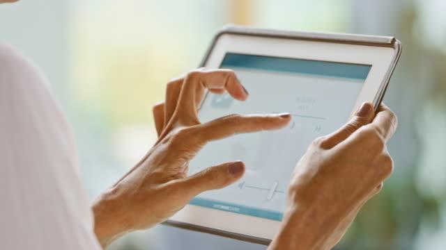 女性彼女の錠剤を服用し、スマート ホームのアプリを使用して、彼女の家を制御するには - セレクティブフォーカス点の映像素材/bロール