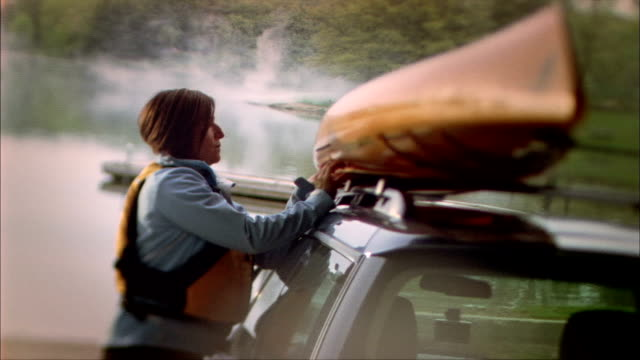 ms pan canted woman taking kayak off roof of car, rock cut state park, rockford, illinois, usa - 積荷を降ろす点の映像素材/bロール