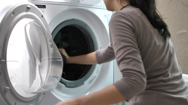 woman taking laundry in washing machine at home - tumble dryer stock videos & royalty-free footage