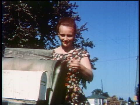 1957 woman taking mail from mailbox outdoors / educational - mailbox stock videos and b-roll footage