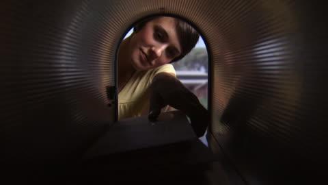 woman taking mail out of mailbox - domestic mailbox bildbanksvideor och videomaterial från bakom kulisserna