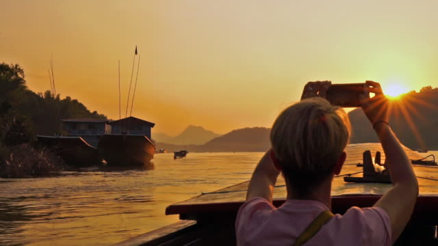 woman taking mobile phone photos on sunset mekong river cruise, laos - cruise vacation stock videos & royalty-free footage