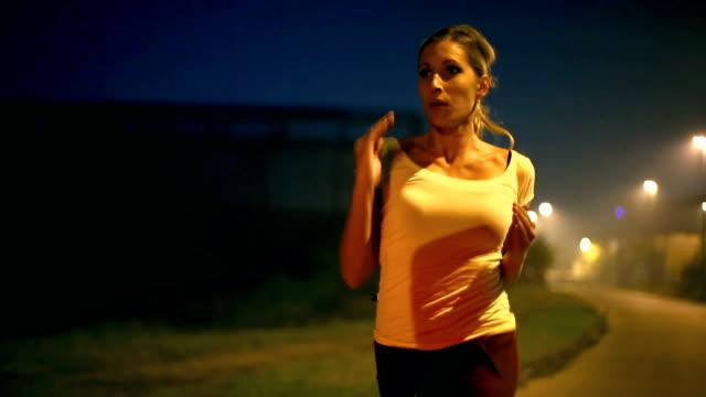 vídeos y material grabado en eventos de stock de mujer tomando la noche para correr en la ciudad. - imagen virada