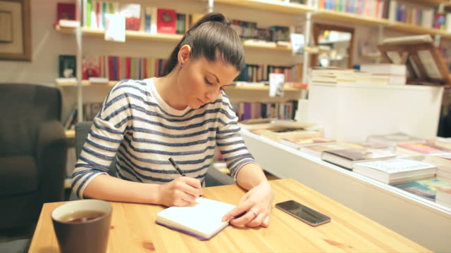 woman taking notes in the bookstore. - pen stock videos and b-roll footage