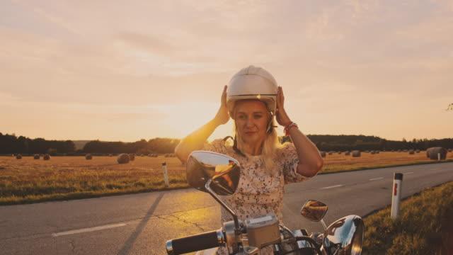 slo mo frau zieht einen helm ab - motorradfahrer stock-videos und b-roll-filmmaterial