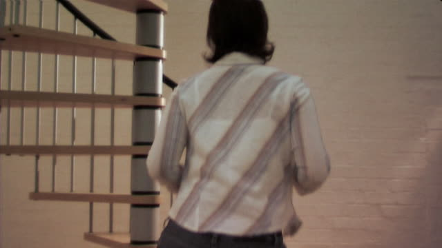 Woman taking off blouse and climbing spiral staircase