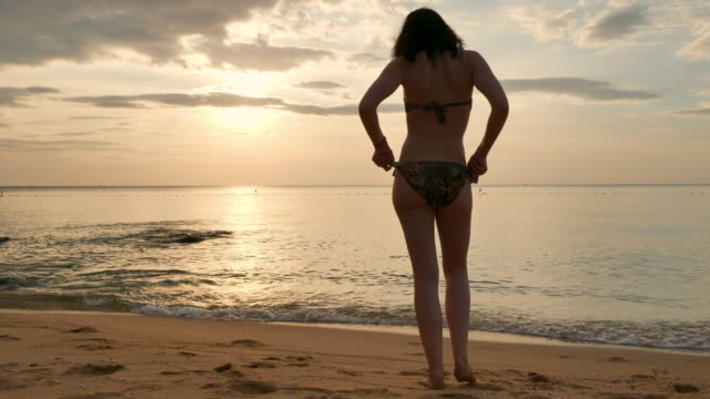 woman taking off shirt and sitting on beach at sunset - undressing stock videos & royalty-free footage