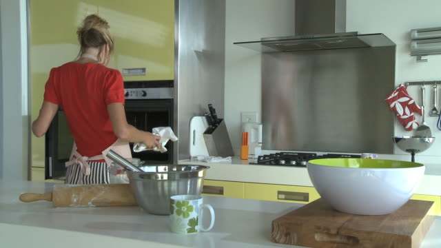 ms woman taking out baking tray of cake from oven / cape town south africa - baking tray stock videos & royalty-free footage