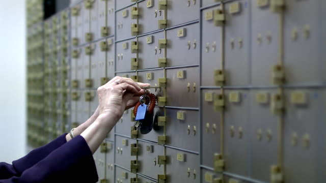 cu selective focus woman taking out one safe-deposit box, bethlehem, pennsylvania, usa - 銀行点の映像素材/bロール