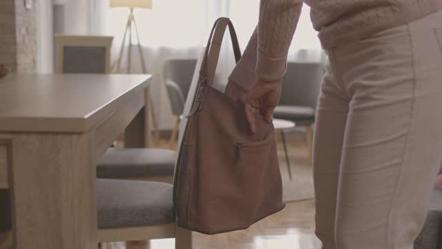 ハンドバッグからスマートフォンを取り出してテーブルの上に置く女性 - バッグ点の映像素材/bロール