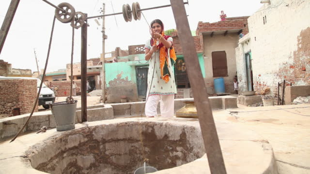 Woman taking out water from well, Faridabad, Haryana, India