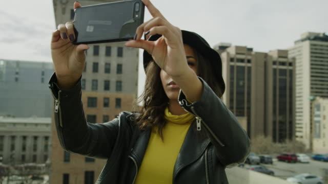 woman taking panoramic photograph of city with cell phone on roof / salt lake city, utah, united states - 回転する点の映像素材/bロール
