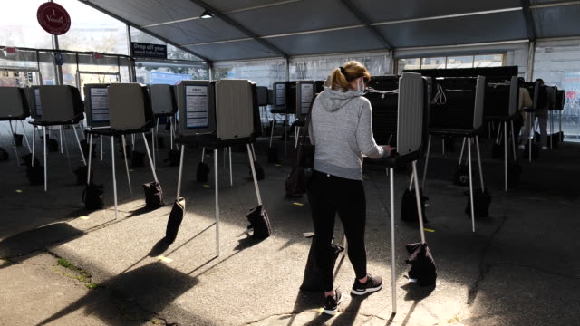 woman taking part in early voting in san francisco. residents cast ballots at an early voting polling location for the 2020 presidential election. in... - 参加者点の映像素材/bロール