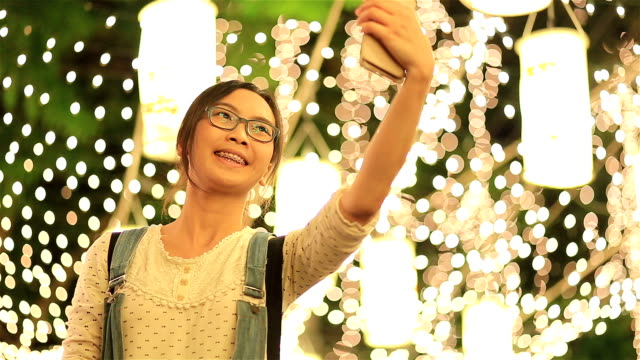 HD: woman taking photo light lamp in night.