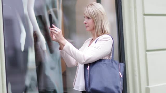 woman taking photo of a store window - quarantenne video stock e b–roll