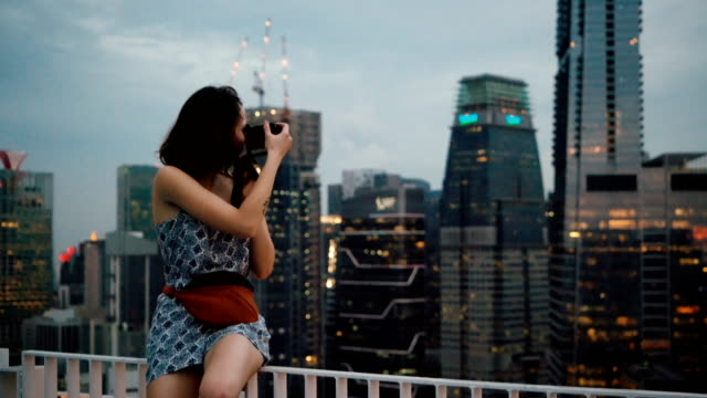 woman  taking photo  of  cityscape of singapore city from view point - fotografo video stock e b–roll