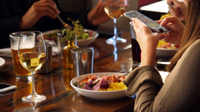 cu woman taking photo of food with smartphone while having lunch with friends in restaurant - meal stock videos & royalty-free footage