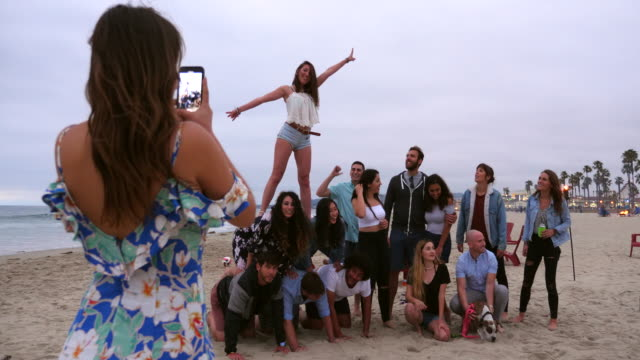 ws woman taking photo of friends making human pyramid during beach party - generation y stock-videos und b-roll-filmmaterial
