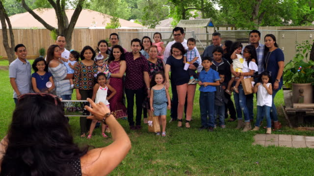 MS HA Woman taking photo of smiling multigenerational family gathered for backyard birthday party